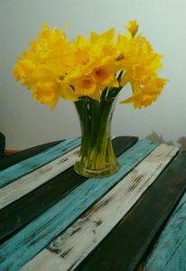 A vase of daffodils on a striped table