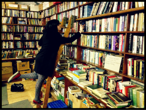 Woman putting a book on stacked shelves